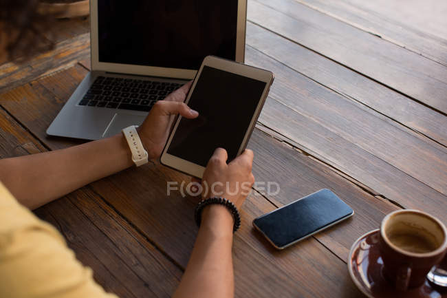 Розділ середині людина, використовуючи цифровий планшетний в кафетерії — стокове фото
