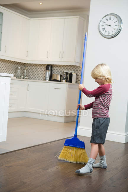 Boy Cleaning Floor With Broom In Kitchen At Home Stock Photo