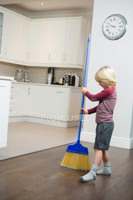 Garçon sol de nettoyage avec balai dans la cuisine à la maison — Photo de stock