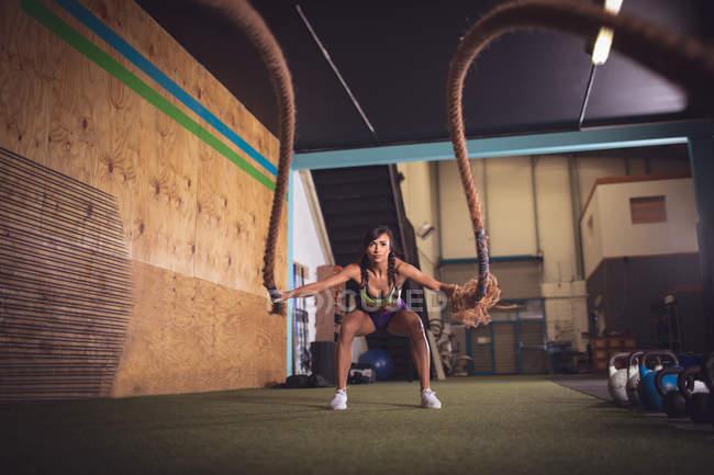 Fit жінка, роблячи битви мотузку вправи в тренажерному залі — стокове фото