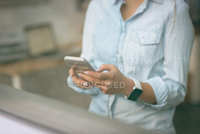 Female executive using mobile phone in office — Stock Photo