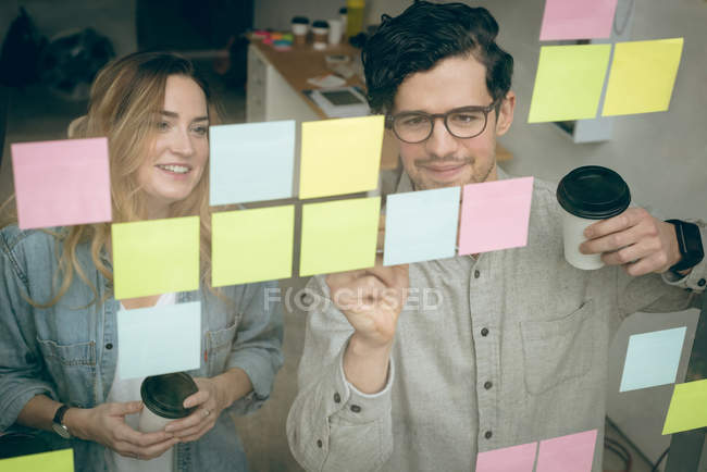 Бізнес колегами, обговорювати над наліпок в офісі — стокове фото