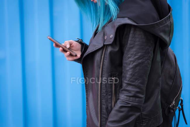 Средняя секция женщины с рюкзаком с помощью мобильного телефона — стоковое фото