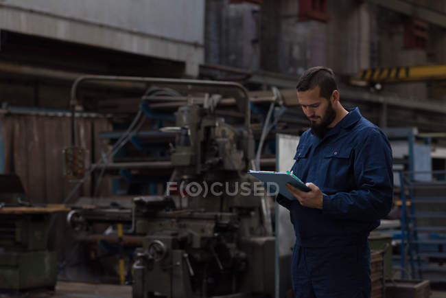 Technician maintaining record on clipboard in metal industry — Stock Photo
