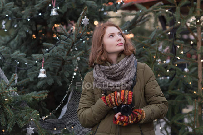 Thoughtful woman in winter clothing holding vintage camera — Stock Photo