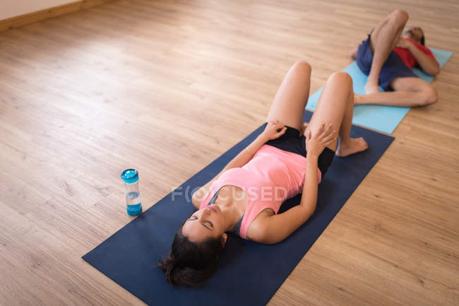 Woman and man meditating together in fitness club — Stock Photo