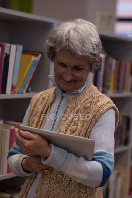 Active senior woman using digital tablet in library — Stock Photo