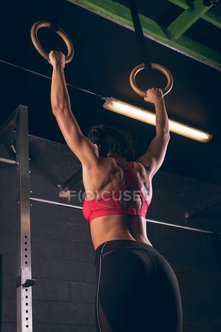 Подтянутая женщина в спортзале подтягивается к гимнастическим кольцам — стоковое фото