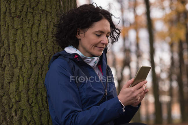 Молода жінка користується мобільним телефоном у парку. — стокове фото