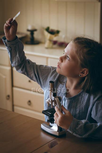 Chica experimentando microscopio deslizante microscopio en casa - foto de stock