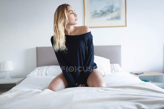 Thoughtful woman sitting on bed in bedroom at home — Stock Photo
