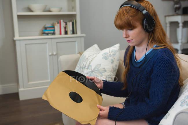 Donna che tiene il disco in vinile in soggiorno a casa — Foto stock