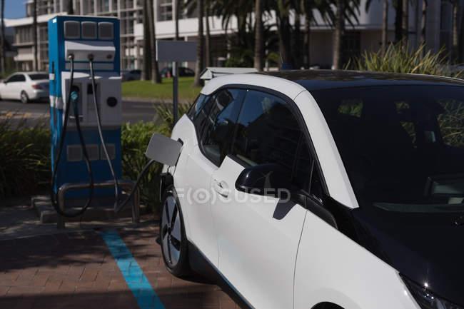 Voiture électrique chargée à la station de recharge par une journée ensoleillée — Photo de stock