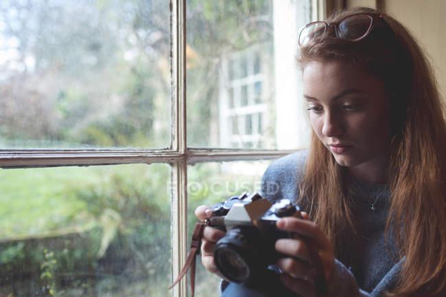 Frau überprüft Bilder auf Retro-Kamera in der Nähe des Fensters zu Hause — Stockfoto