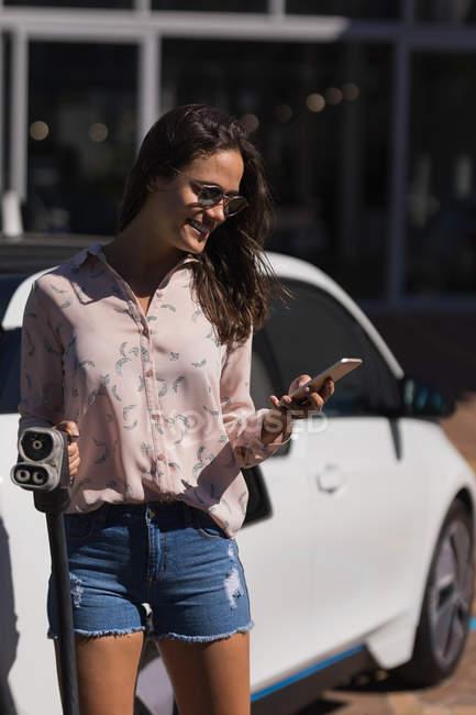 Frau benutzt Handy beim Halten von Ladestecker an Ladestation — Stockfoto