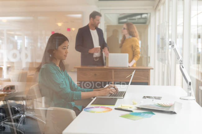 Progettista grafico femminile utilizzando computer portatile allo scrittorio in ufficio — Foto stock