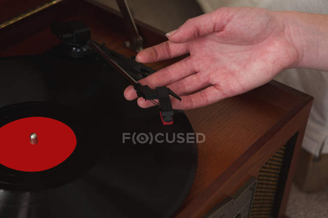 Close-up of woman playing a gramophone at home — Stock Photo