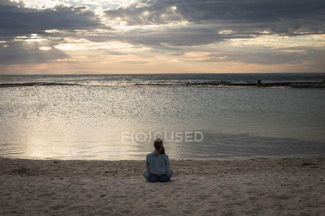 Rear view of woman sitting on a beach at dusk — Stock Photo