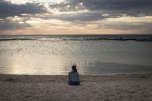 Visão traseira da mulher sentada em uma praia ao entardecer — Fotografia de Stock