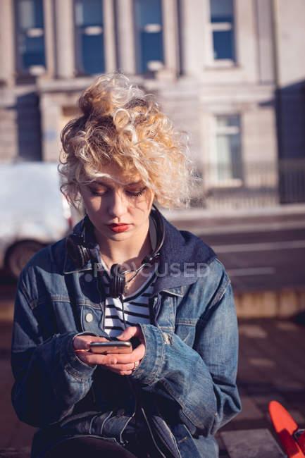 Молода жінка, що використання мобільного телефону у міській вулиці — стокове фото