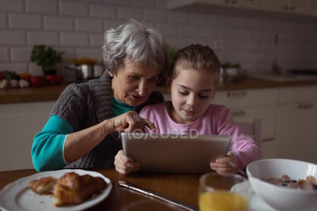Grand-mère et petite-fille utilisant une tablette numérique dans la cuisine à la maison — Photo de stock