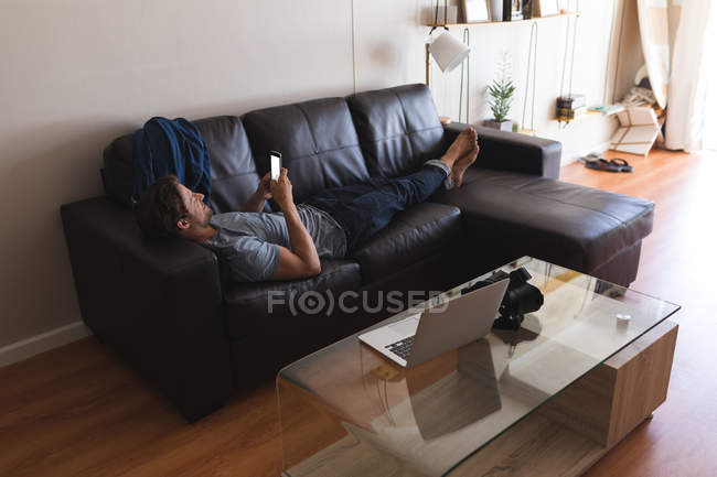 Man using mobile phone in living room at home — Stock Photo