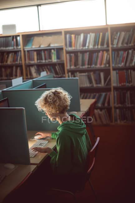 Giovane donna che lavora sul computer in biblioteca — Foto stock