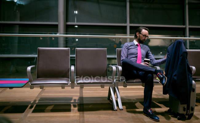 Бизнесмен пьет кофе во время ожидания в зале ожидания в аэропорту — стоковое фото