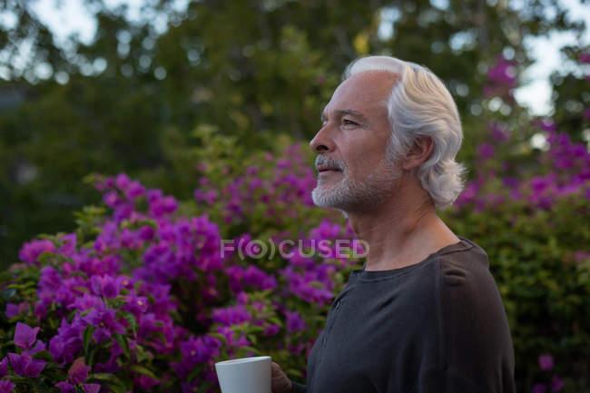 Задумчивый пожилой человек пьет кофе на балконе — стоковое фото