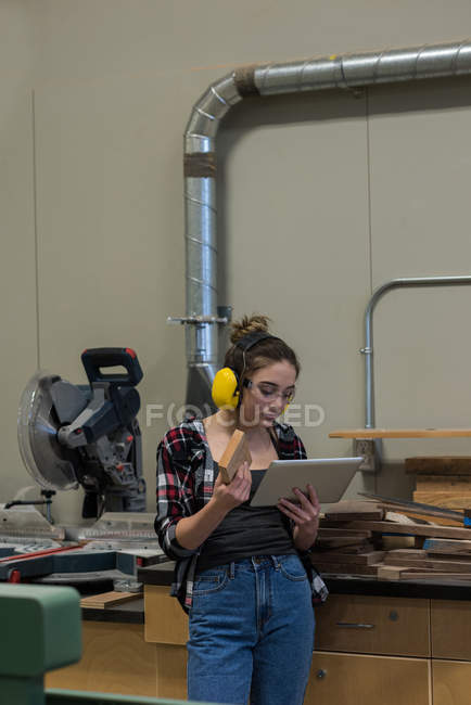 Female carpenter examining a piece of wood while using digital tablet at workshop — Stock Photo