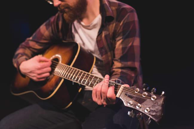 Человек, играл на гитаре на сцене в театре — стоковое фото