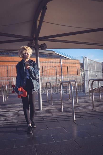 Молода жінка за допомогою мобільного телефону на вулиці — стокове фото