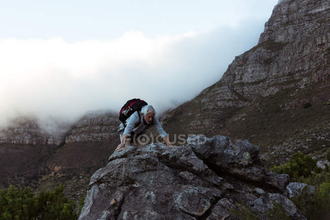 Senior man climbing rocky mountain at countryside — Stock Photo