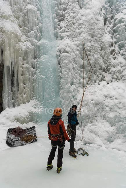 Casal de pé juntos perto da montanha rochosa durante o inverno — Fotografia de Stock