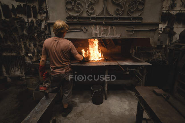 Blacksmith heating metal rod in fire — Stock Photo