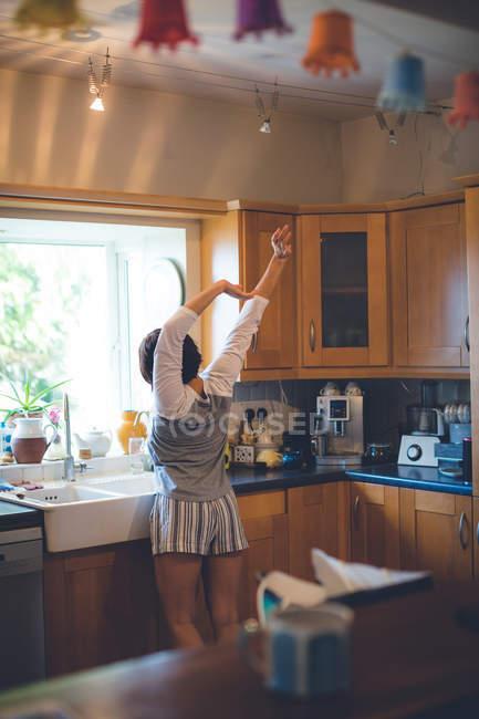 Вид сзади женщины, стоящей с поднятыми руками на кухне дома — стоковое фото