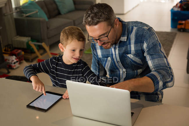 Father and son using laptop and digital tablet at home — Stock Photo