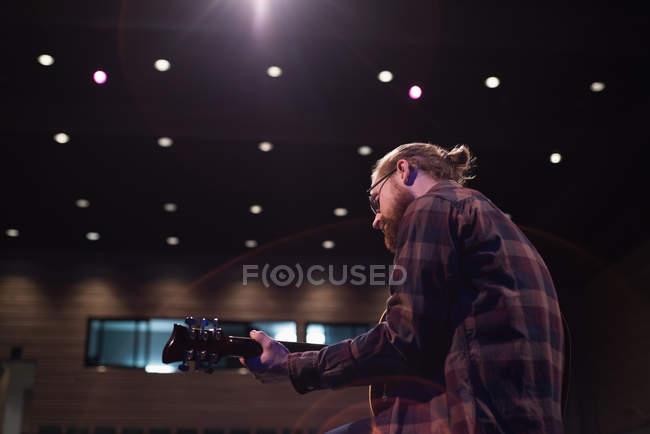 Человек, играл на гитаре на сцене театра — стоковое фото
