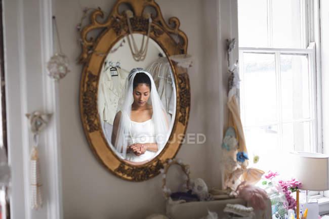 Reflexo da jovem noiva vestida de noiva no espelho — Fotografia de Stock
