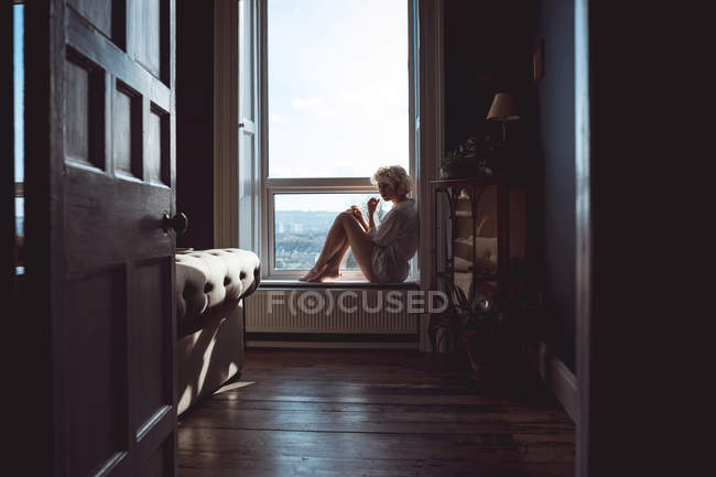 Thoughtful woman sitting near window at home — Stock Photo