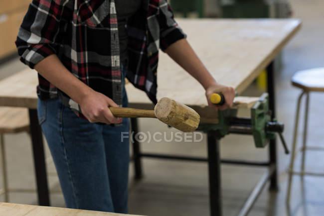 Розділ середині жіночий Карпентер, використовуючи долото з молотом на шматок дерева на семінарі — стокове фото