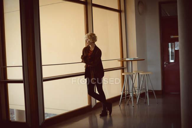 Nachdenkliche Frau stand in der Nähe von Fenster — Stockfoto
