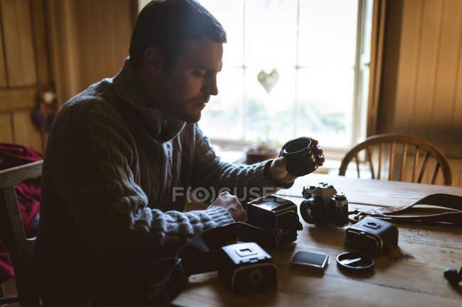Homem reparando uma câmera vintage em casa — Fotografia de Stock