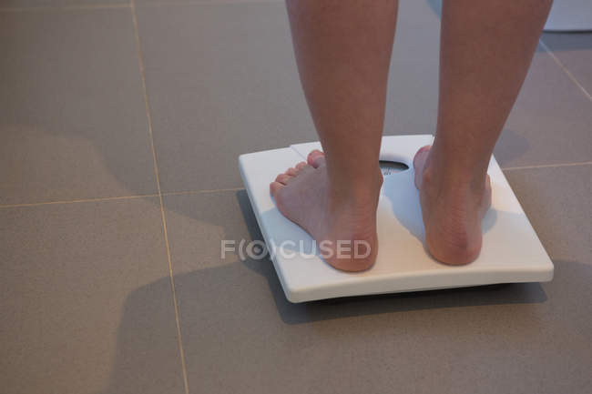 Sezione bassa della donna che controlla il suo peso sulle bilance a casa — Foto stock