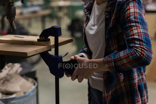 Средняя часть женского плотника с помощью винтового зажима на куске дерева в мастерской — стоковое фото