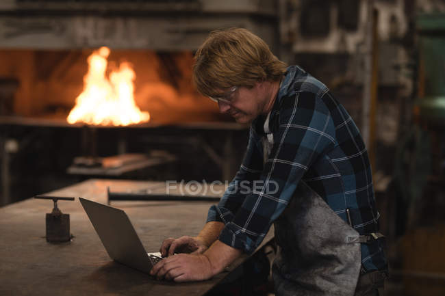 Attentive blacksmith using laptop in workshop — Stock Photo