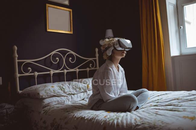 Жінка за допомогою віртуальної реальності гарнітуру в спальні в домашніх умовах — стокове фото