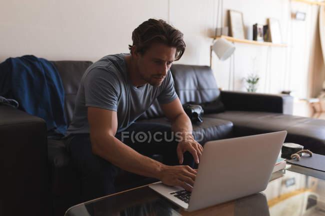 Mann benutzt Laptop im heimischen Wohnzimmer — Stockfoto