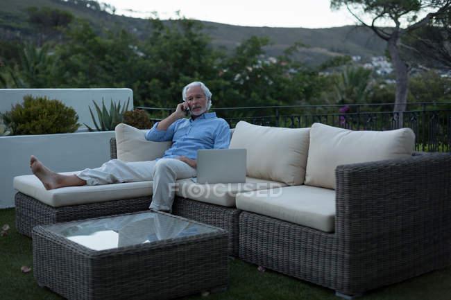 Homme âgé parlant sur un téléphone portable dans le balcon à la maison — Photo de stock