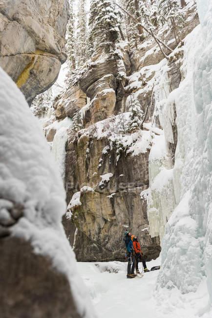 Couple debout ensemble près de la montagne rocheuse pendant l'hiver — Photo de stock